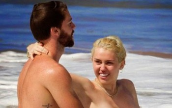 Miley Cyrus goes topless as she frolics in the ocean with boyfriend