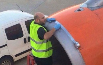 Shocked issue - A passenger snaps airport worker using tape on plane engine just the moments before take-off