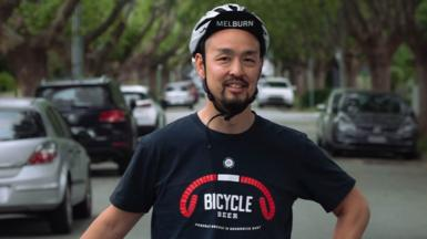 Man standing in street wearing bike helmet